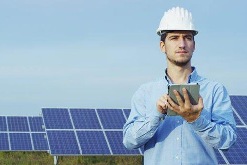 Worker reviewing work on a tablet surrounded by solar panels.
